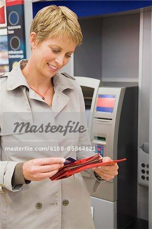 Femme, mettre une carte de crédit dans son portefeuille et souriant