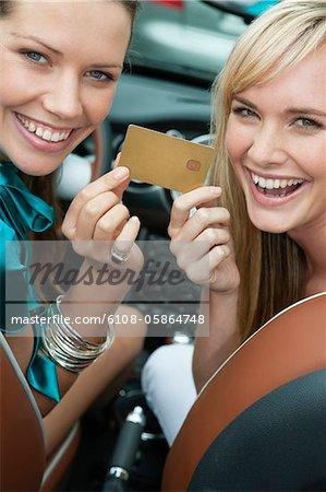 Zwei Frauen zeigen eine Kreditkarte im Auto