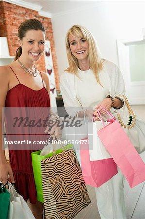 Zwei Frauen holding Einkaufstaschen in eine Boutique und Lächeln