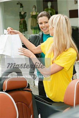 Zwei Frauen Lächeln in der Nähe ein Auto nach dem Einkaufen