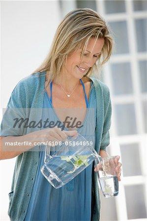 Femme en versant l'eau dans un verre