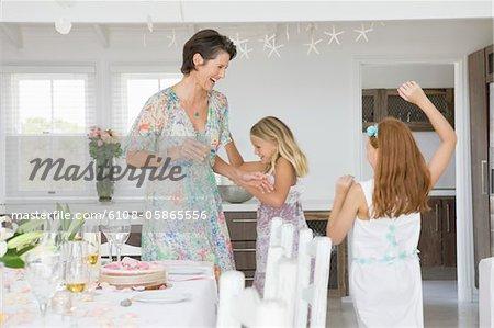 Femme debout avec ses filles jouer à une table à manger