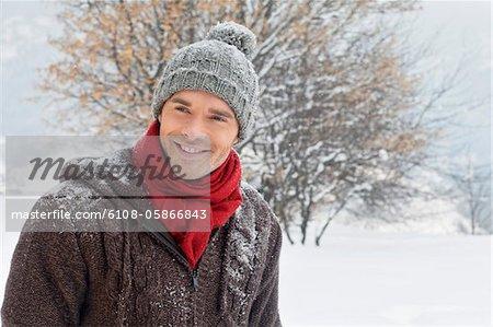 Junger Mann in Winterkleidung lächelnd in die Kamera