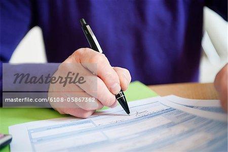 Homme remplit son formulaire d'impôt