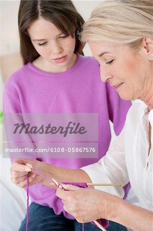 Femme enseigner sa petite-fille à tricoter