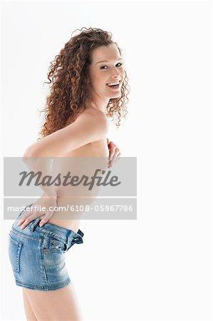 Portrait d'une femme debout avec une main sur la hanche et souriant