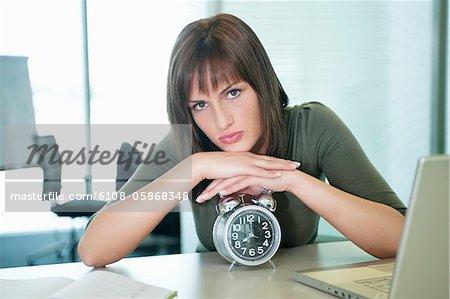 Portrait d'une femme d'affaires s'appuyant sur un radio-réveil