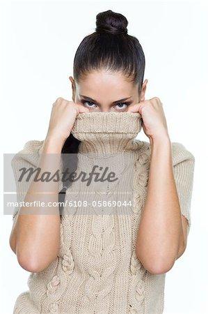 Jeune femme couvrant son visage avec pull
