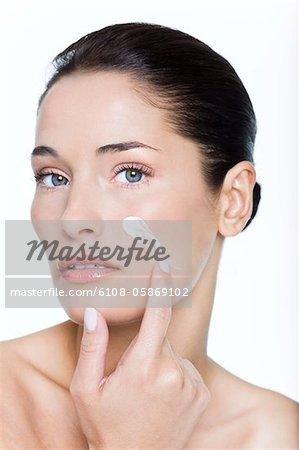 Junge Frau Anwendung Feuchtigkeitscreme