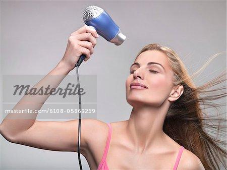 Jeune femme à l'aide d'un sèche-cheveux