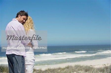 Homme embrassant une femme par derrière sur la plage