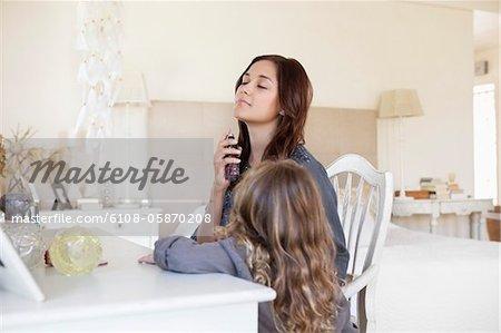 Junge Frau während ihrer Tochter neben ihr Parfüm anwenden