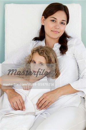Porträt einer jungen Frau mit ihrer Tochter in weißen Tuch eingewickelt liegen