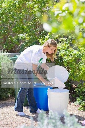 Frau Papiere in die Mülltonne werfen