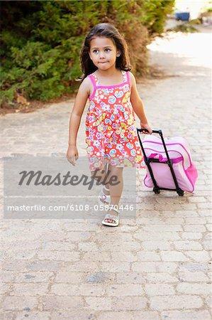 Petite fille en tirant un sac