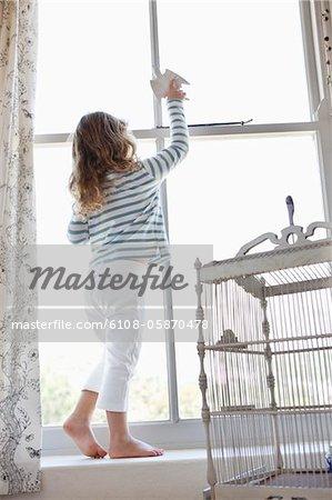 Niedliche kleine Mädchen spielen mit einem Spielzeug Vogel am Fenster