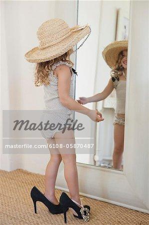 Adorable petite fille habillée comme sa mère en accessoires surdimensionnés et en regardant le miroir
