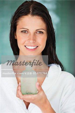 Portrait d'une femme tenant une bouteille d'huile aromathérapie et souriant