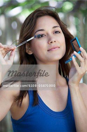 Beautiful young Woman applying eyeshadow