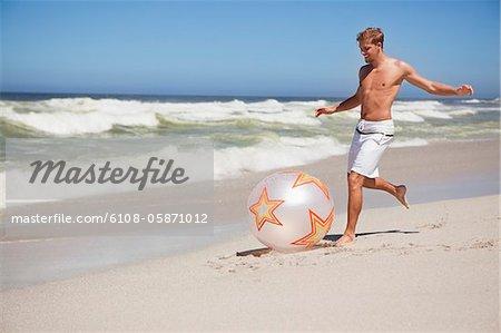 Homme de botter le ballon sur la plage