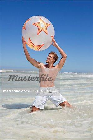 Homme qui joue avec le ballon de plage