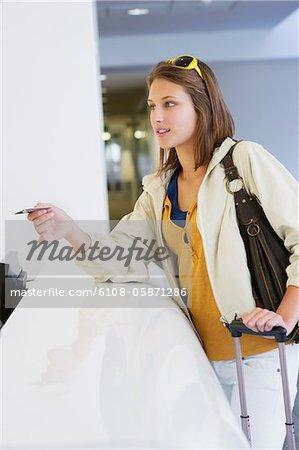 Frau mit einer Kreditkarte an einer Hotelrezeption