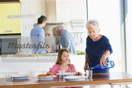 Femme senior, verser l'eau dans un verre à une table à manger