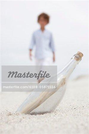 Blurred boy walking towards bottle with note inside on beach