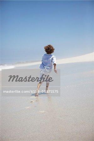 Rear view of a boy running on beach