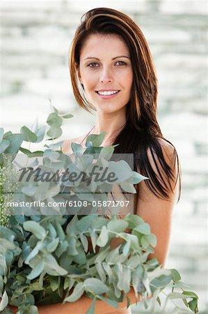 Porträt einer Frau hält Blätter und Lächeln
