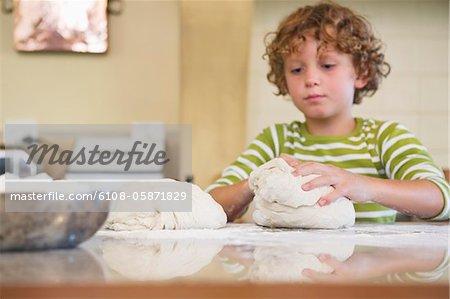 Süße kleine Junge kneten Teig in Küche