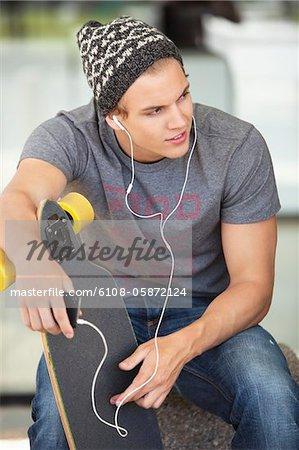Man hält ein Skateboard und Anhören von Musik auf dem Handy