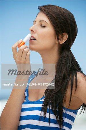 Femme application de baume pour les lèvres