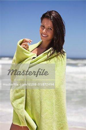 Porträt einer Frau, eingewickelt in ein Handtuch am Strand