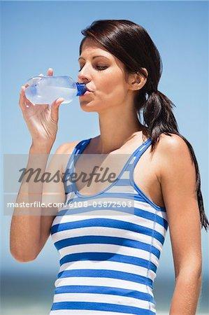 Gros plan d'une femme l'eau potable provient d'une bouteille d'eau sur la plage