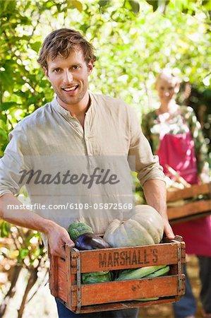 Homme tenant un cageot de légumes souriant