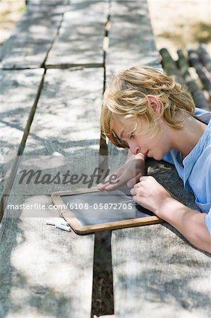 Side profile of a little boy writing on slate outdoors