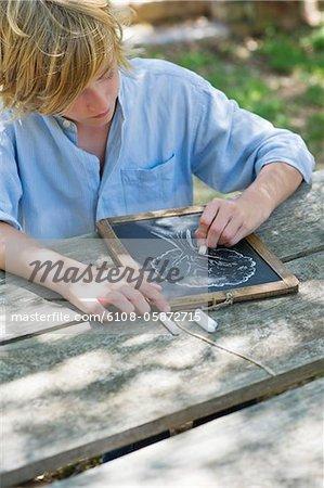 Little boy making drawing of tree on slate outdoors