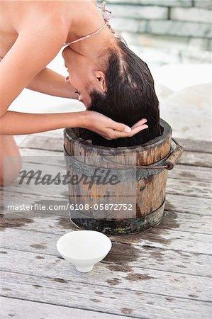 Frau Haare waschen, in einen Eimer