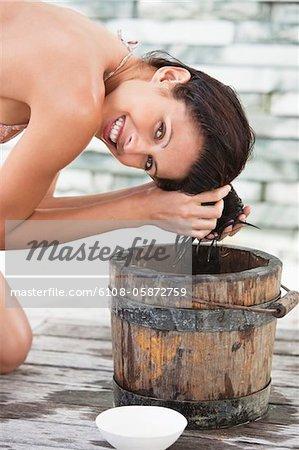 Porträt einer Frau, die Haare waschen, in einen Eimer