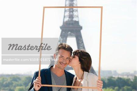 Couple encadrant leurs vacances de rêve avec la tour Eiffel en arrière-plan, Paris, Ile-de-France, France