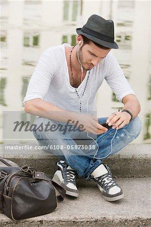 Man sitzt auf der Kante eines Kanals und hören von Musik mit einem MP3-Player, Paris, France, Frankreich