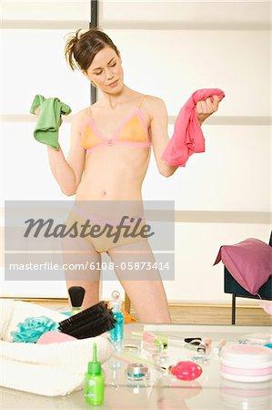 Junge Frau in Unterwäsche zögern zwischen 2 Kleidung