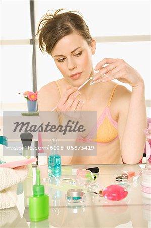 Jeune femme en lingerie avec une brosse de maquillage