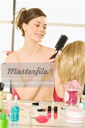 Jeune femme souriante en sous-vêtements brossage perruque