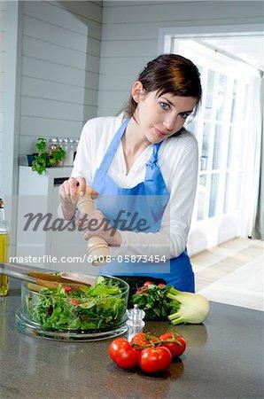 Jeune femme assaisonner une salade