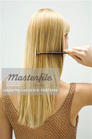 Blonde Frau, ihr Haar zu kämmen
