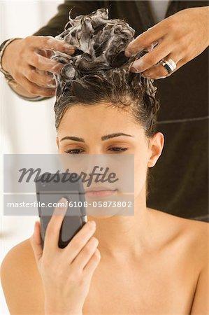Frau telefonieren und haben die Haare vom Friseur
