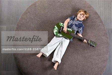 Junge auf einem runden Sofa liegend und eine Gitarre spielen