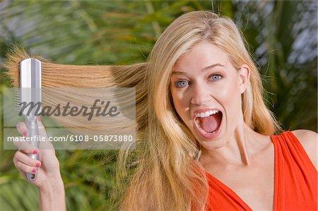 Frau, ihr Haar zu Bürsten und schreien